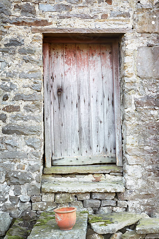 A wooden door on the side of a stone building by James Ross for Stocksy United