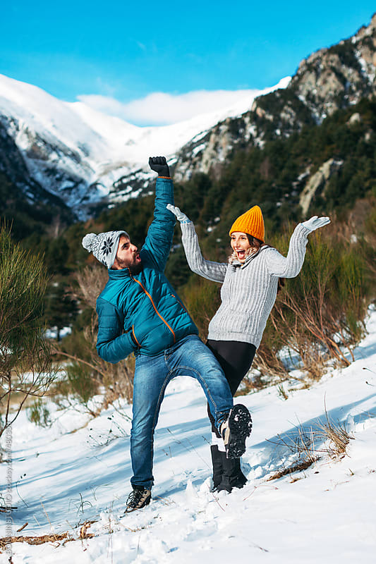 Young couple having fun on a snowy winter day at the mountain. by BONNINSTUDIO for Stocksy United