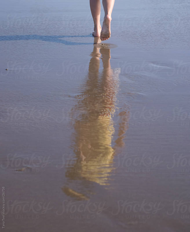 The reflection of a young girl walking along the ocean beach by Tana Teel for Stocksy United