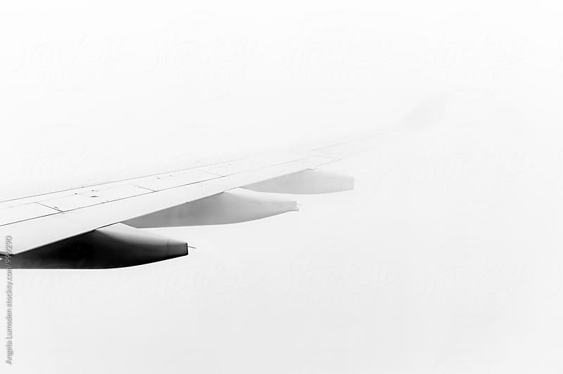 Airplane wing disppearing into cloud by Angela Lumsden for Stocksy United