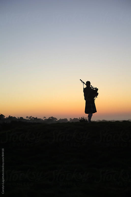 Silhouette of a bagpipe player at sunset by Carolyn Lagattuta for Stocksy United