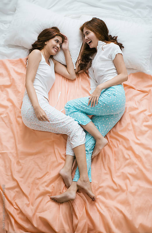 Casual beautiful Asian twin sisters on the pastel bed sheet by Nabi Tang for Stocksy United
