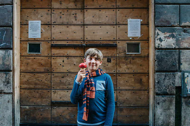 Smiling boy with red ice cream against wooden door by Trent Lanz for Stocksy United