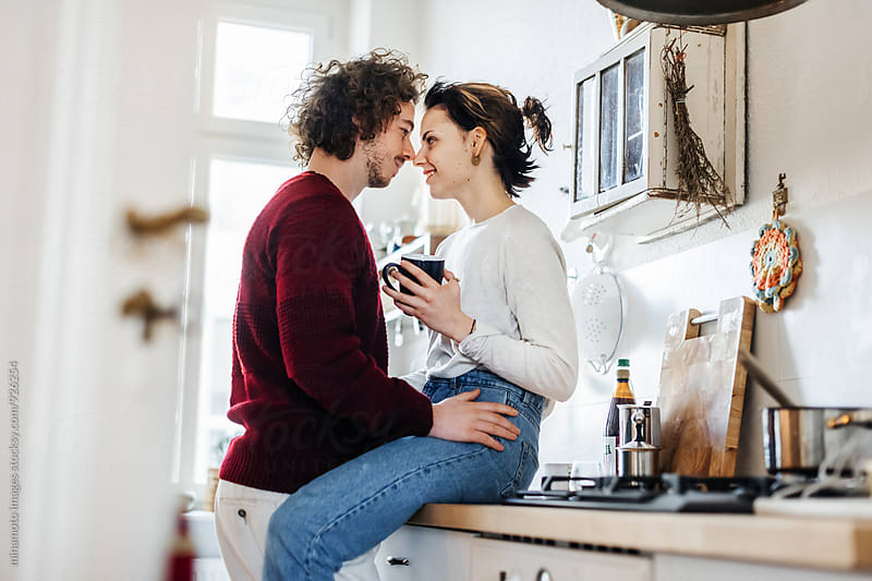 A young couple hugging in a kitchen. by minamoto images for Stocksy United