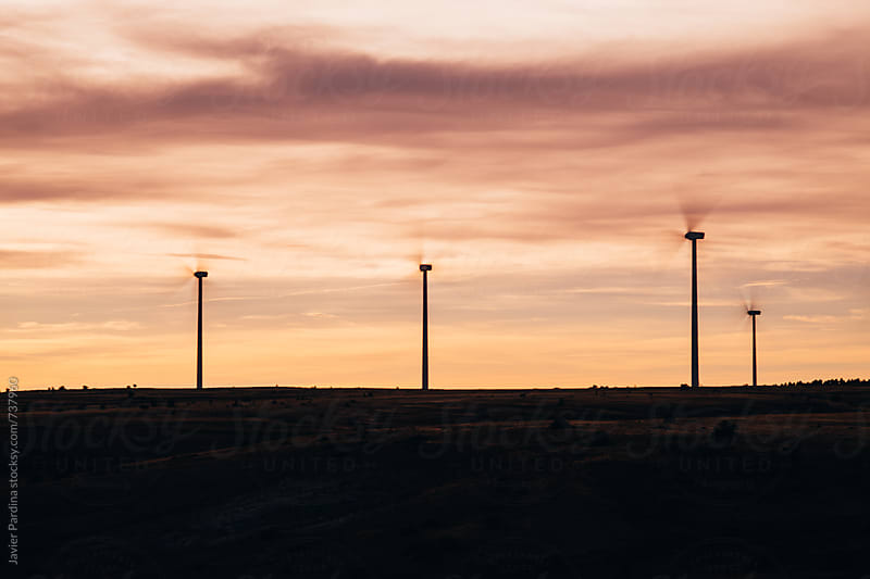 windmills at sunset by Javier Pardina for Stocksy United