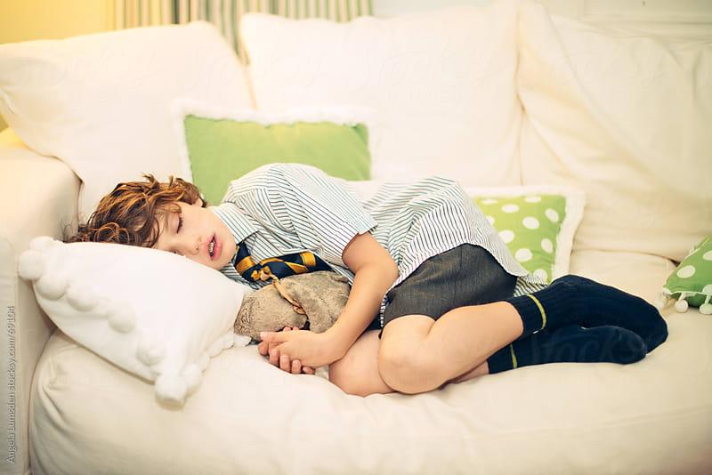 Boy asleep on a couch in school uniform by Angela Lumsden for Stocksy United