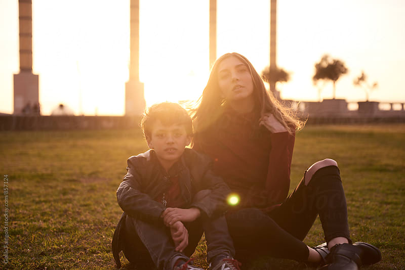 Older sister and her brother sitting on grass at sunset by Guille Faingold for Stocksy United