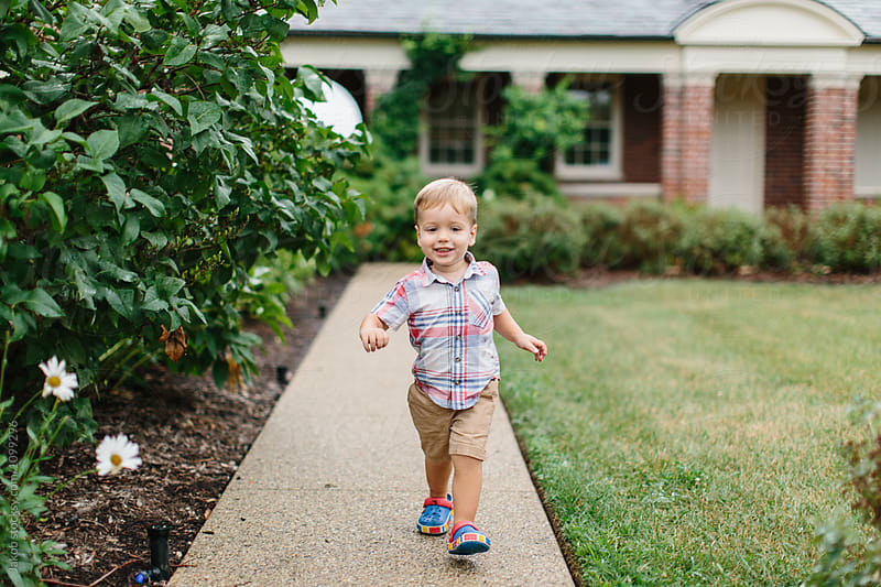 Cute young boy walking around in a courtyard by Jakob for Stocksy United