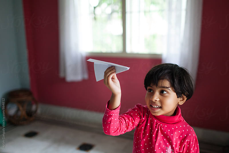 Little girl playing with paper plane by Saptak Ganguly for Stocksy United