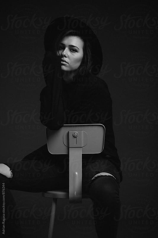 Woman Sitting with Hat by Adrian Ragasa for Stocksy United