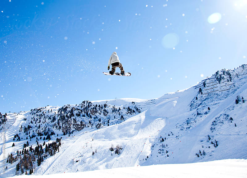 Snowboarder jumping huge while snow is flying through the air by Ivo de Bruijn for Stocksy United