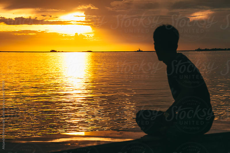 Silhouette of a man at sunset in Manila bay, Philippines by Alejandro Moreno de Carlos for Stocksy United
