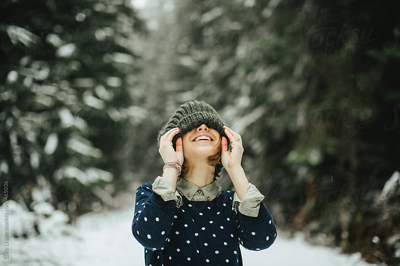 Young fashionable women laughing in the snow by Luke Liable for Stocksy United