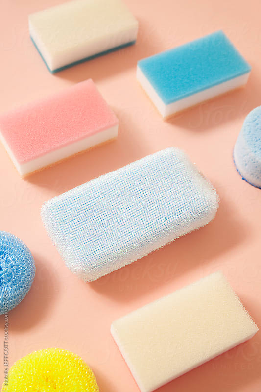 Collection of household cleaning sponges on a pink background by Natalie JEFFCOTT for Stocksy United