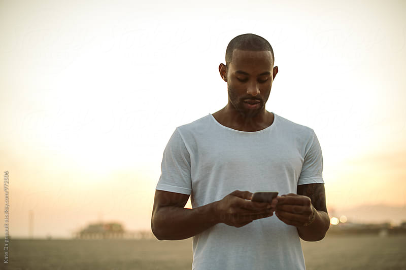 Young handsome black man looking at his phone by Kate Daigneault for Stocksy United