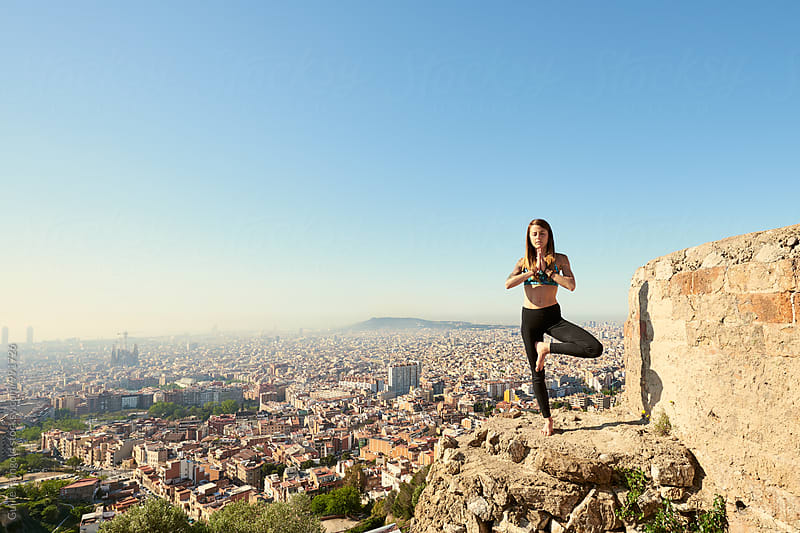 Sportswoman in tree pose against of Barcelona cityscape by Guille Faingold for Stocksy United