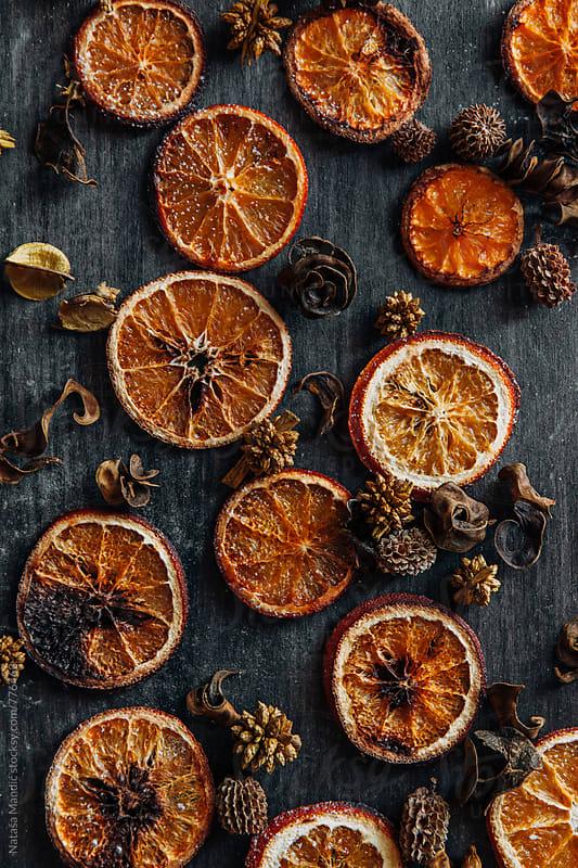 Dried oranges on a dark blackground by Nataša Mandić for Stocksy United