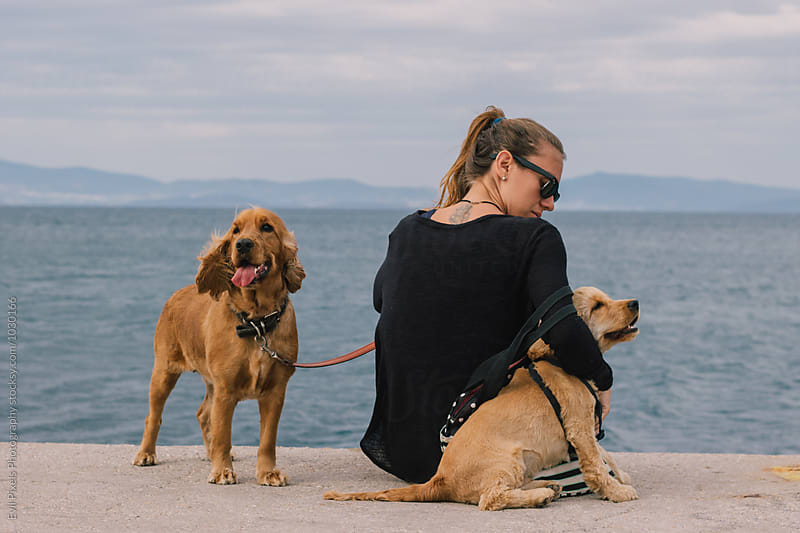 Young female with her cocker spaniels near sea by Evil Pixels  Photography for Stocksy United