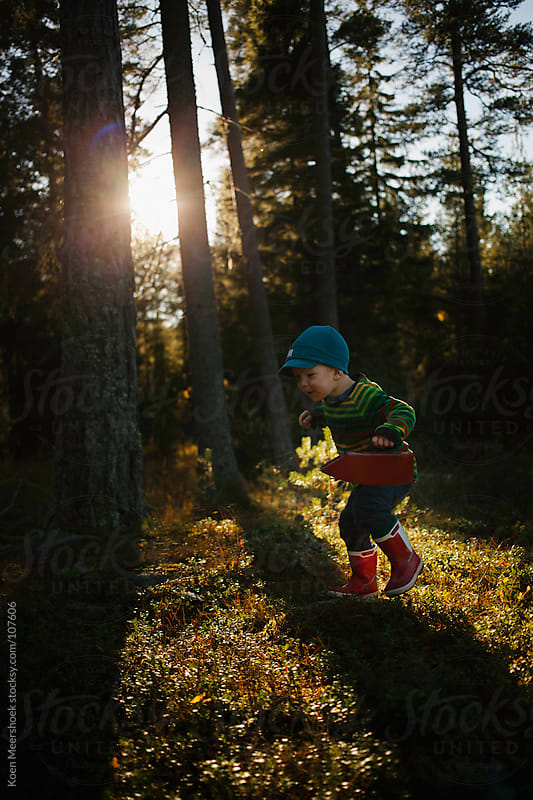 Cute little boy with red boots running in the forest. by Koen Meershoek for Stocksy United