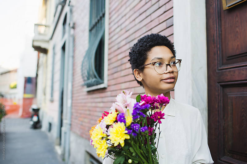 Young and beautiful woman holding a bouquet of flower outside the house by michela ravasio for Stocksy United