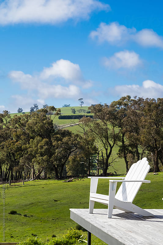 Timber chairs on deck of country home by Rowena Naylor for Stocksy United
