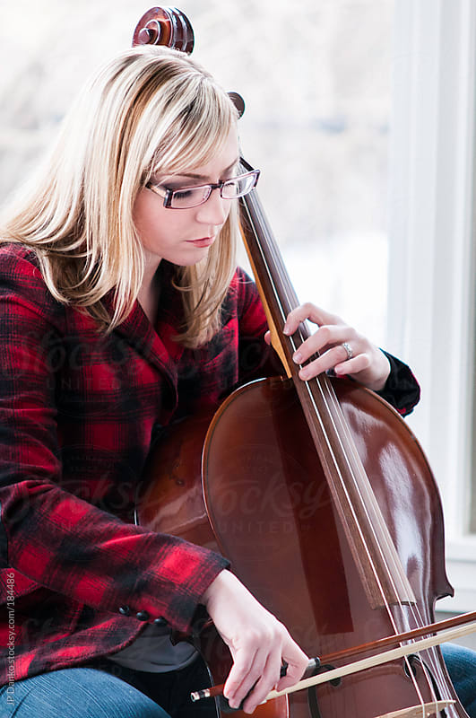 Woman In Plaid Jacket Jeans and Glasses Learning to Play the Cello by JP Danko for Stocksy United
