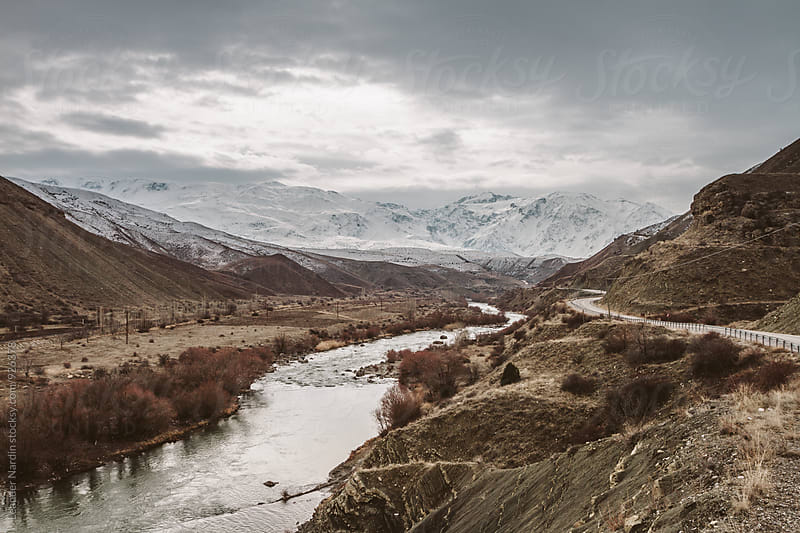 remote valley with a river and a road leading to snowcovered mountain range by Leander Nardin for Stocksy United
