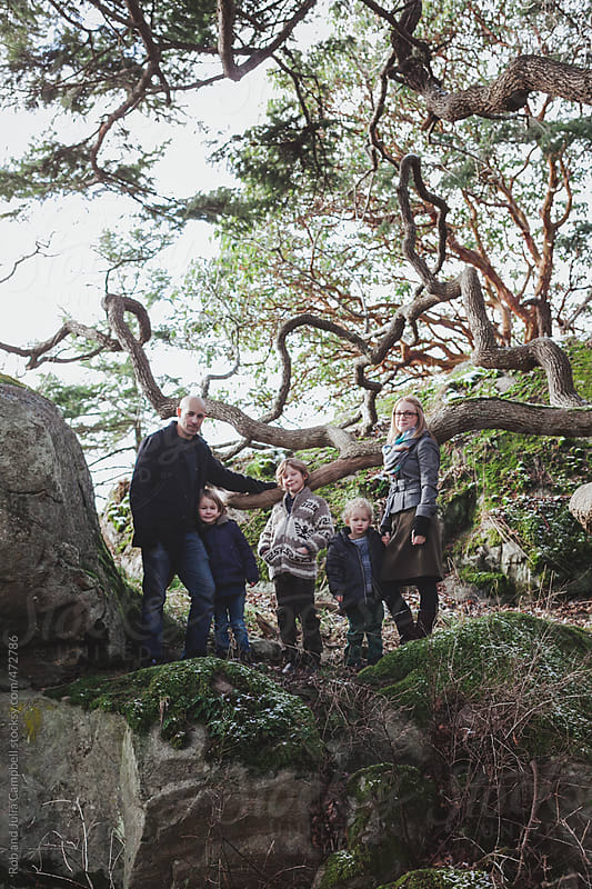 Happy young family posing for portrait outside in winter - rocks and trees by Rob and Julia Campbell for Stocksy United