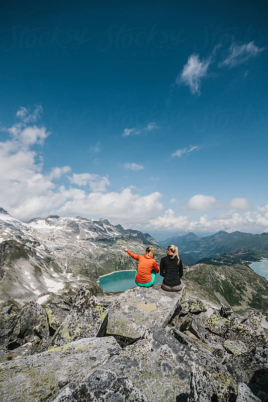 two sporty female hiking friends sitting in high alpine scenery by Leander Nardin for Stocksy United
