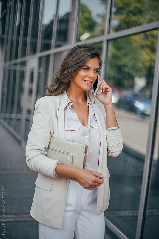 Series of a business woman in the city. Beautiful brunette sitting in coffee shop and working on com by Studio Firma for Stocksy United