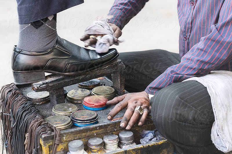 Business man having his shoes polished by a Shoeshiner by RG&B Images for Stocksy United