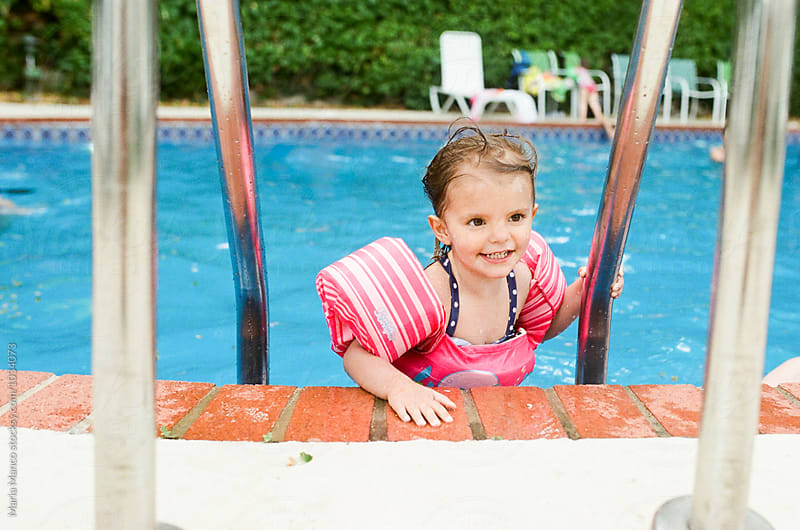 little girl in floaties at the pool by Maria Manco for Stocksy United