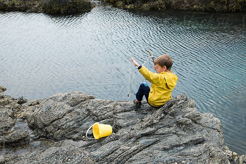 little boy sitting on rock by the sea with a fishing pole by Léa Jones for Stocksy United