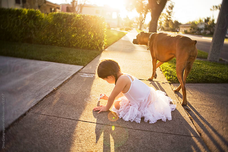 Little Girl Wearing White Slip Dress With Her Dog on Sidewalk by Dina Giangregorio for Stocksy United