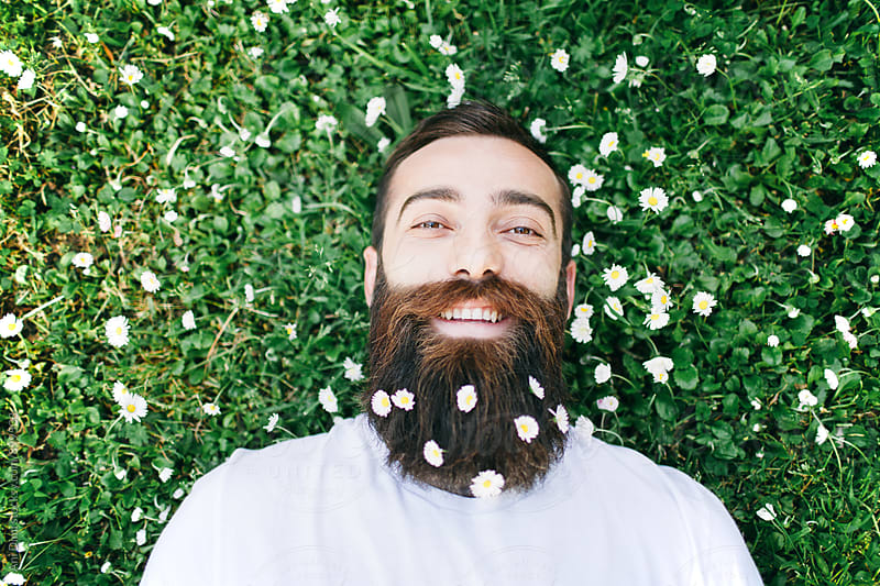 Man with white flowers in a beard by Ani Dimi for Stocksy United