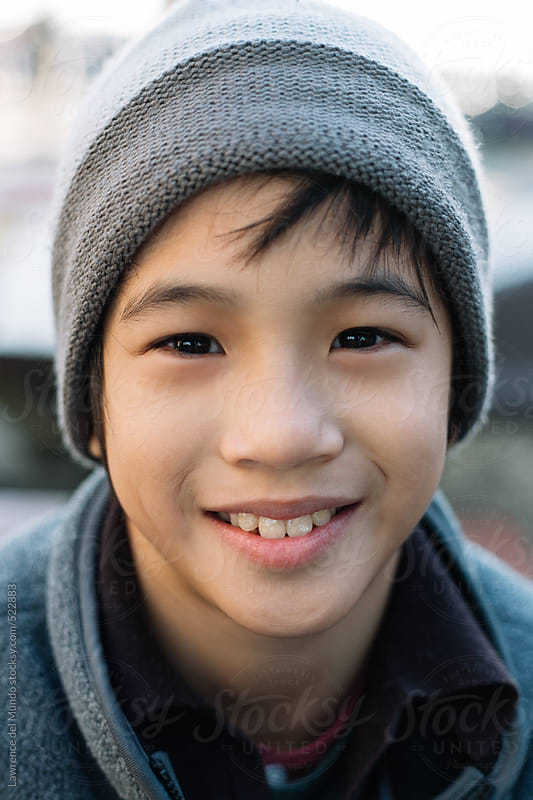 Portrait of a 10 year old boy smiling and looking at camera by Lawrence del Mundo for Stocksy United
