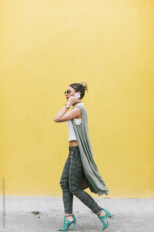 Woman walking and talking on her mobile phone  by Marija Kovac for Stocksy United