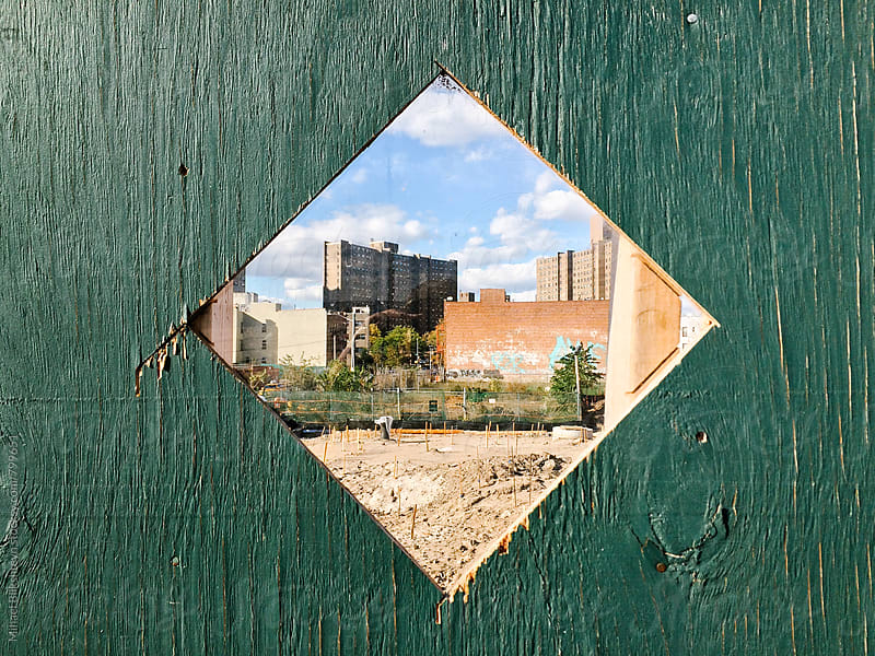 View of a construction site and an abandoned empty lot through a window in a wooden fence by Mihael Blikshteyn for Stocksy United