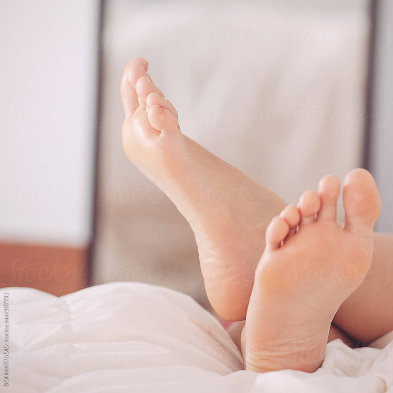 Feet's woman relaxing on the bed. by BONNINSTUDIO for Stocksy United