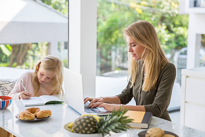 Mom working on her laptop while daughter doing her homework by Jovo Jovanovic for Stocksy United