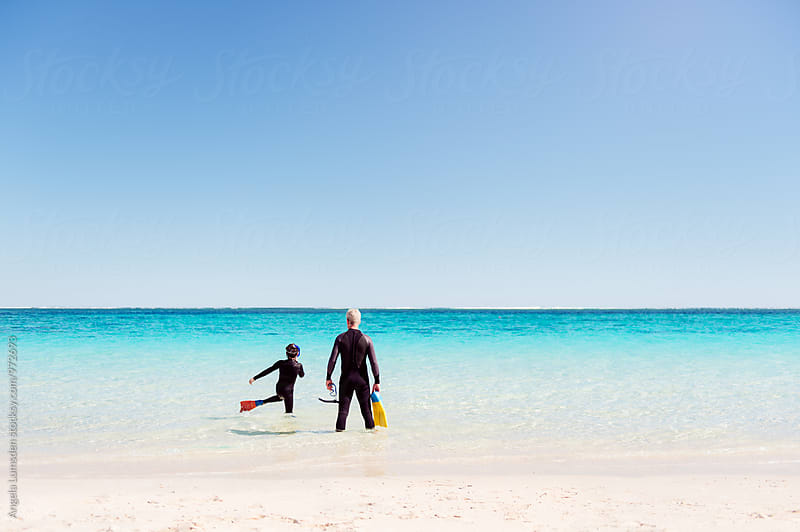 Father and son wearing wetsuits and snorkel gear about to go explore coral reef on the Ningaloo Coast in Western Australia by Angela Lumsden for Stocksy United