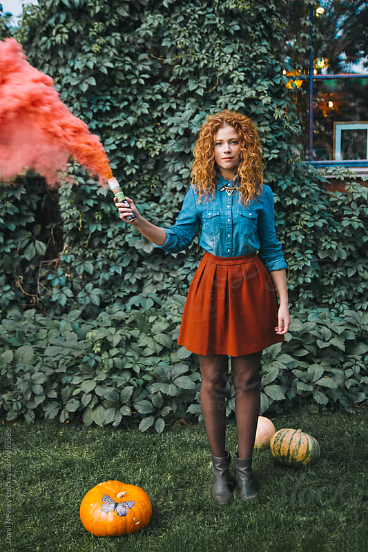 Woman holding colorful smoke bomb by Danil Nevsky for Stocksy United