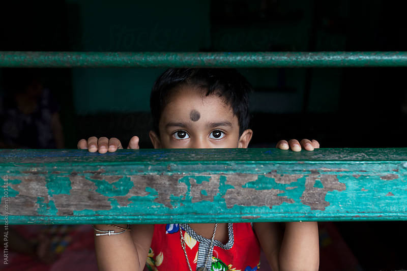 Little girl behing the window and looking at camera by PARTHA PAL for Stocksy United