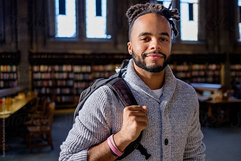 Male African American college student in the library by Suprijono Suharjoto for Stocksy United