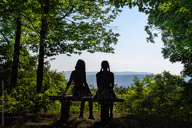 Two silhouetted girls contemplating the view by Deirdre Malfatto for Stocksy United