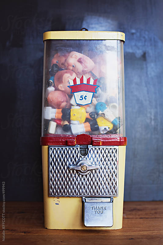 A vintage gumball machine filled with old toys and doll faces by Natalie JEFFCOTT for Stocksy United