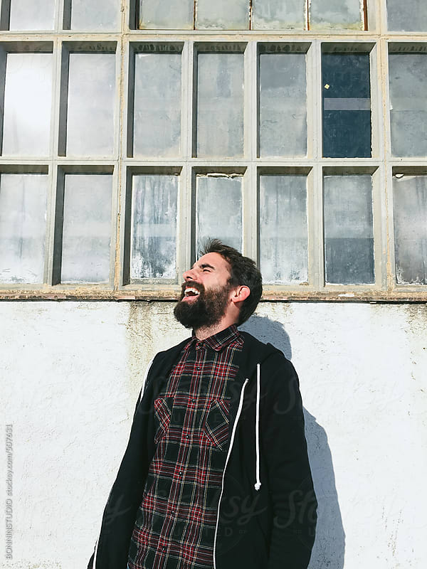 Laughing bearded man in front a old factory window. by BONNINSTUDIO for Stocksy United