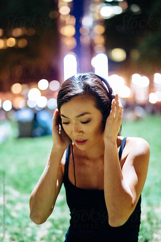 Woman listening music at the park at night by Good Vibrations Images for Stocksy United