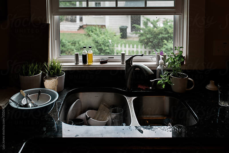 dirty dishes in a sink by Léa Jones for Stocksy United