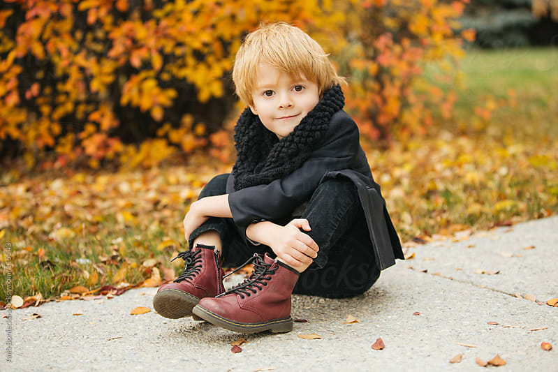 A bright eyed little boy sitting on a sidewalk holding his legs smiling by Ania Boniecka for Stocksy United